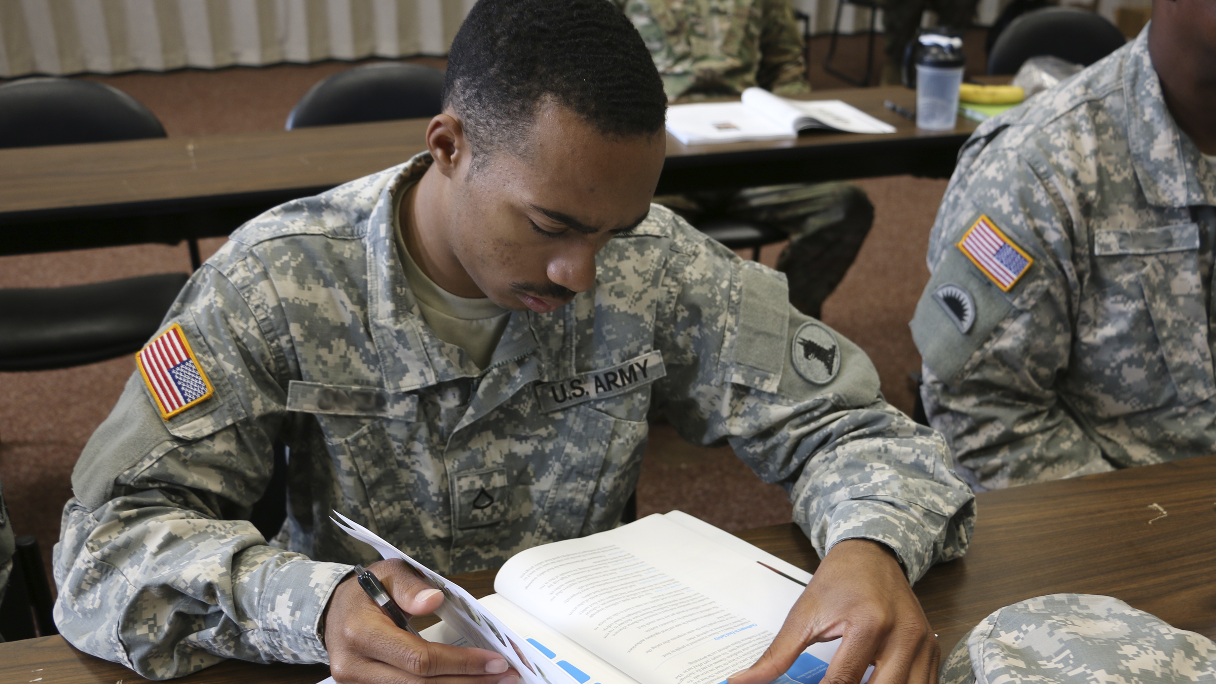 Soldier studying from a textbook