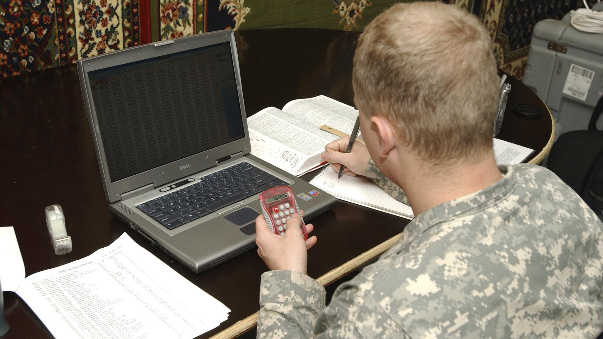 Man in uniform looking over numbers with calculator