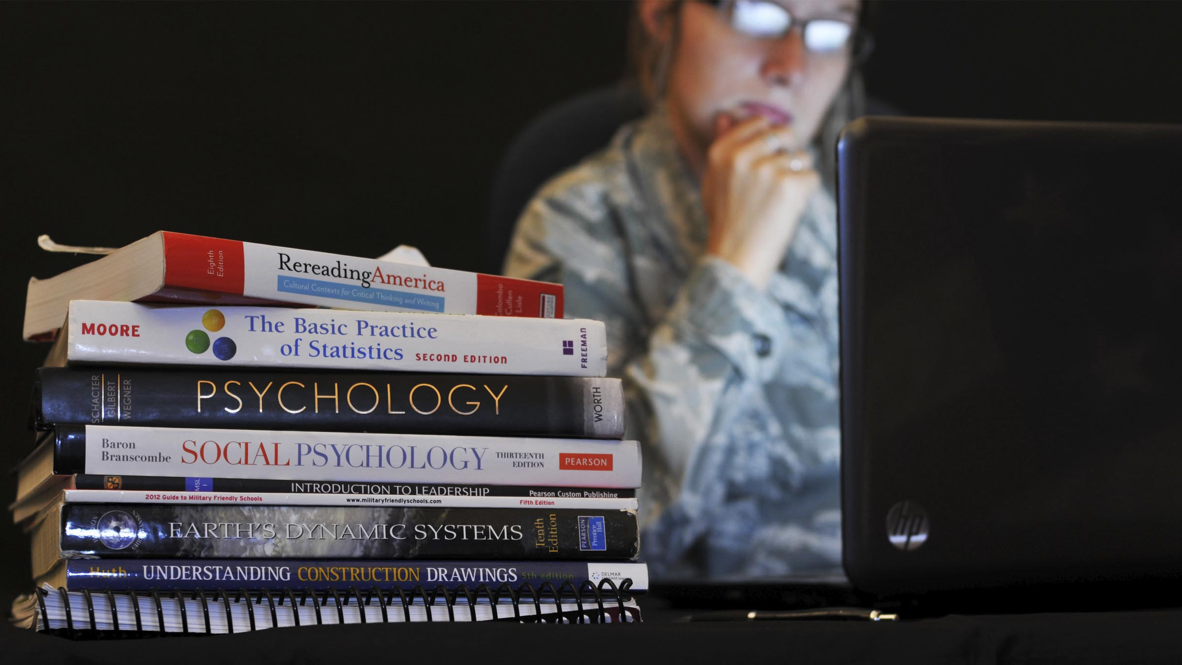 Pile of textbooks and service member in background