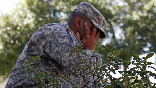 Service member hides face in their hands