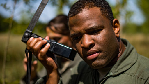 A male Air Force captain listens to a radio during an outdoor training exercise.