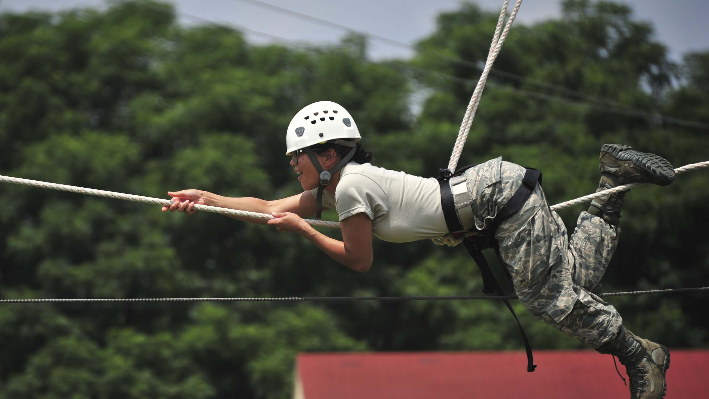 Service member pulls herself across a rope