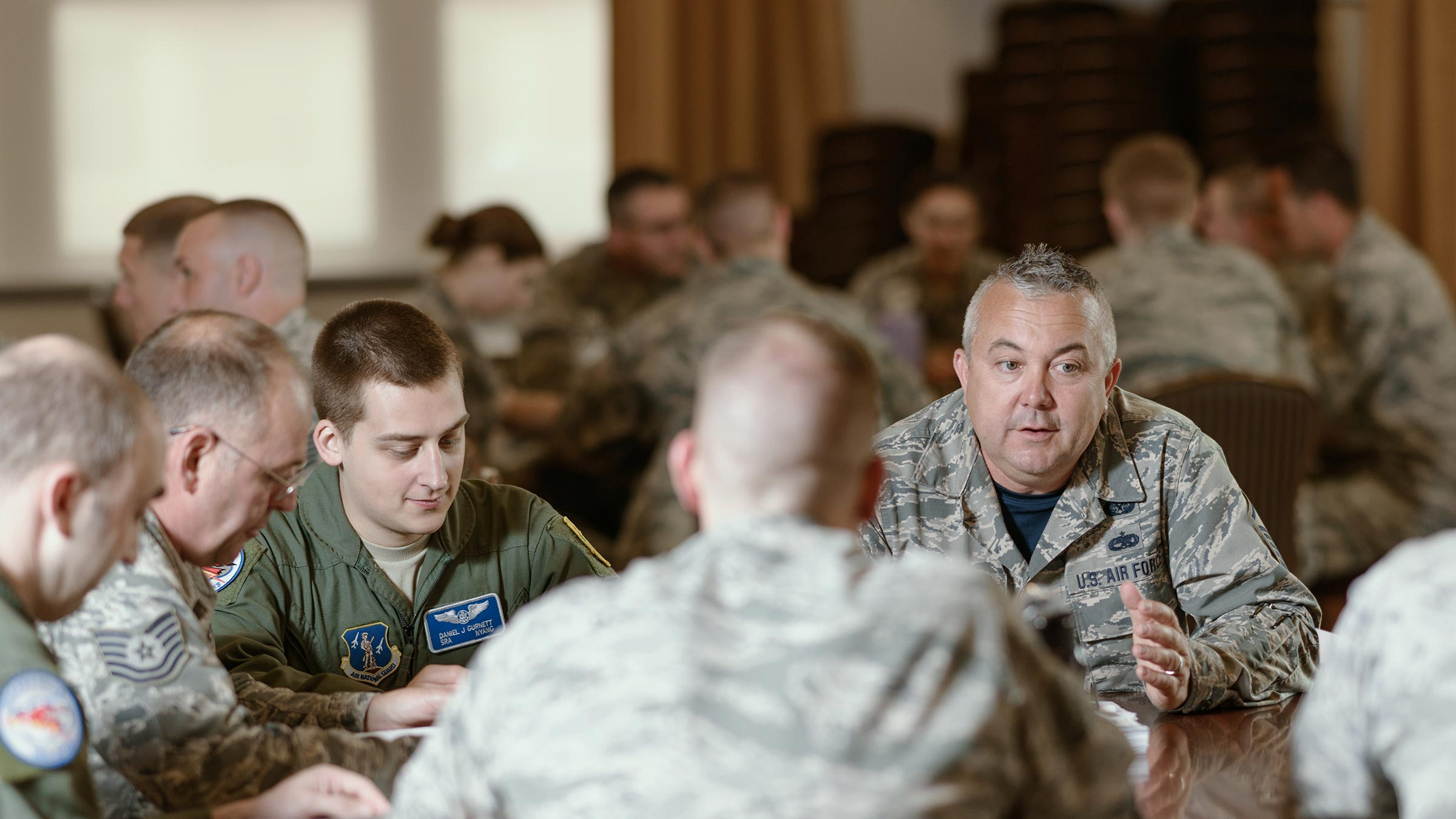 Service members discuss around table