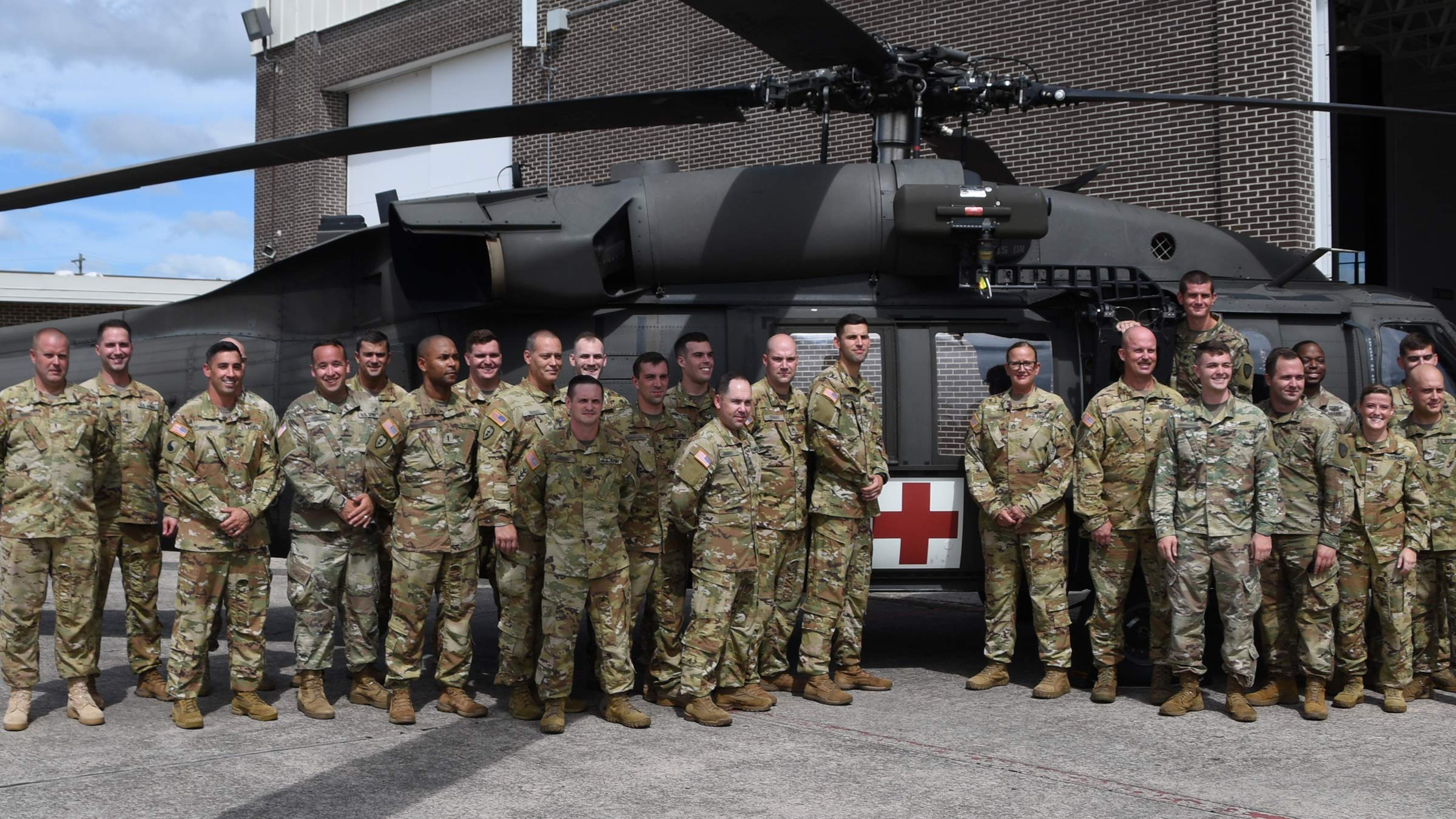 service memebers pose in front of helicopter