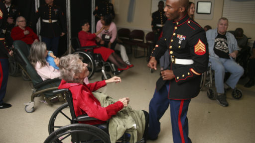 Service member and woman in wheelchair dancing