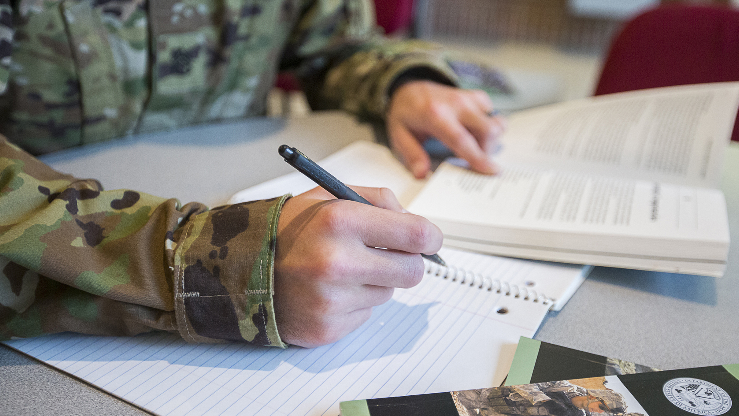 Service member takes notes while reading a book.