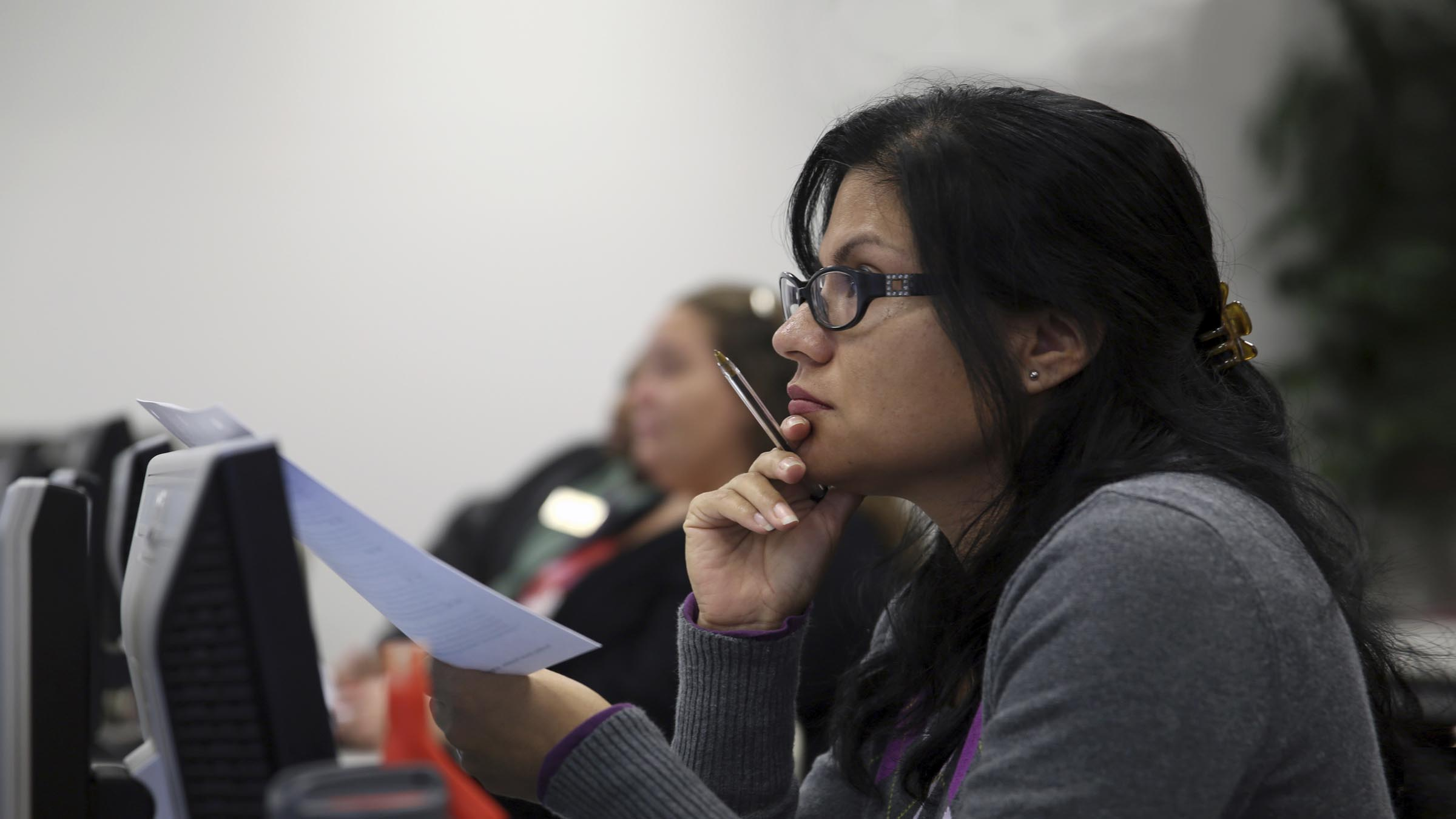 Woman with papers in hand listening to speaker