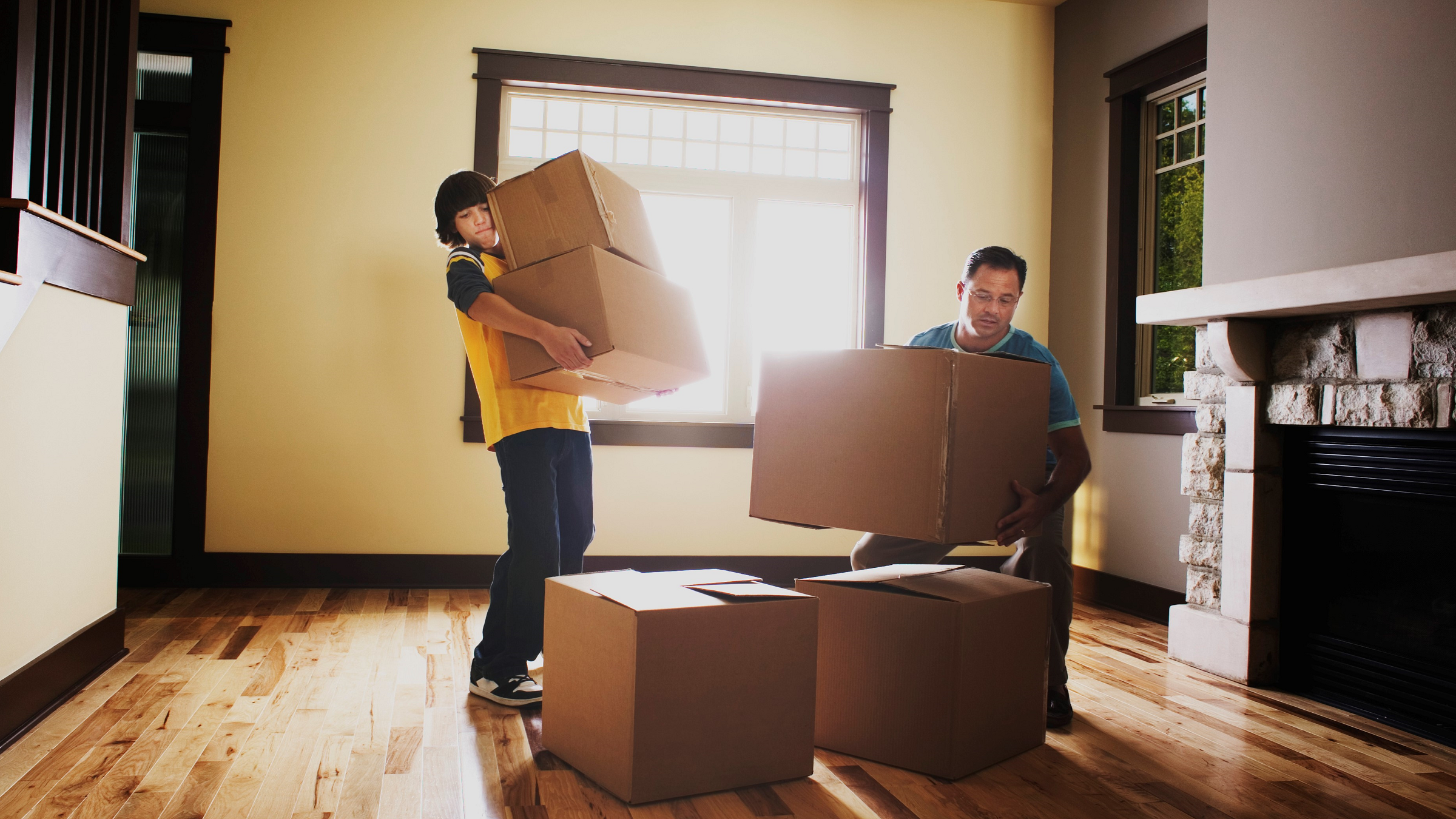 Father and son stacking moving boxes.