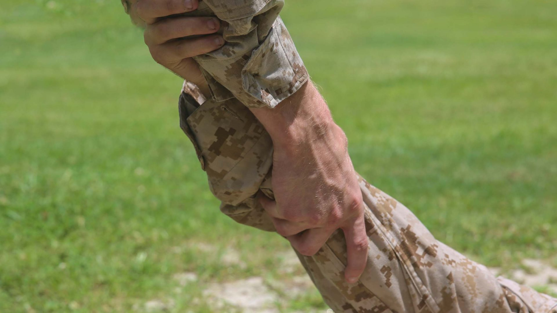 Servicemember reaching out and helping up another.