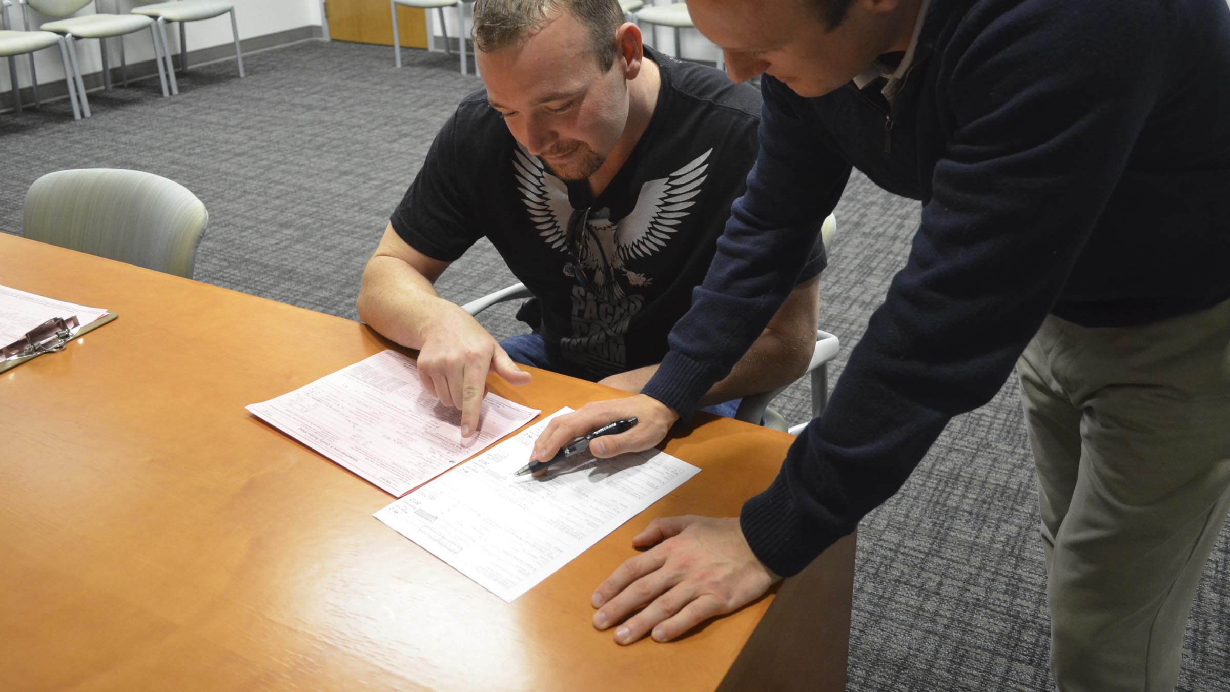 Man helping another man with filing paperwork