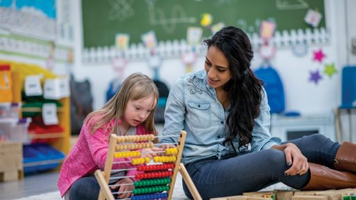 Teacher working with special needs child in classroom
