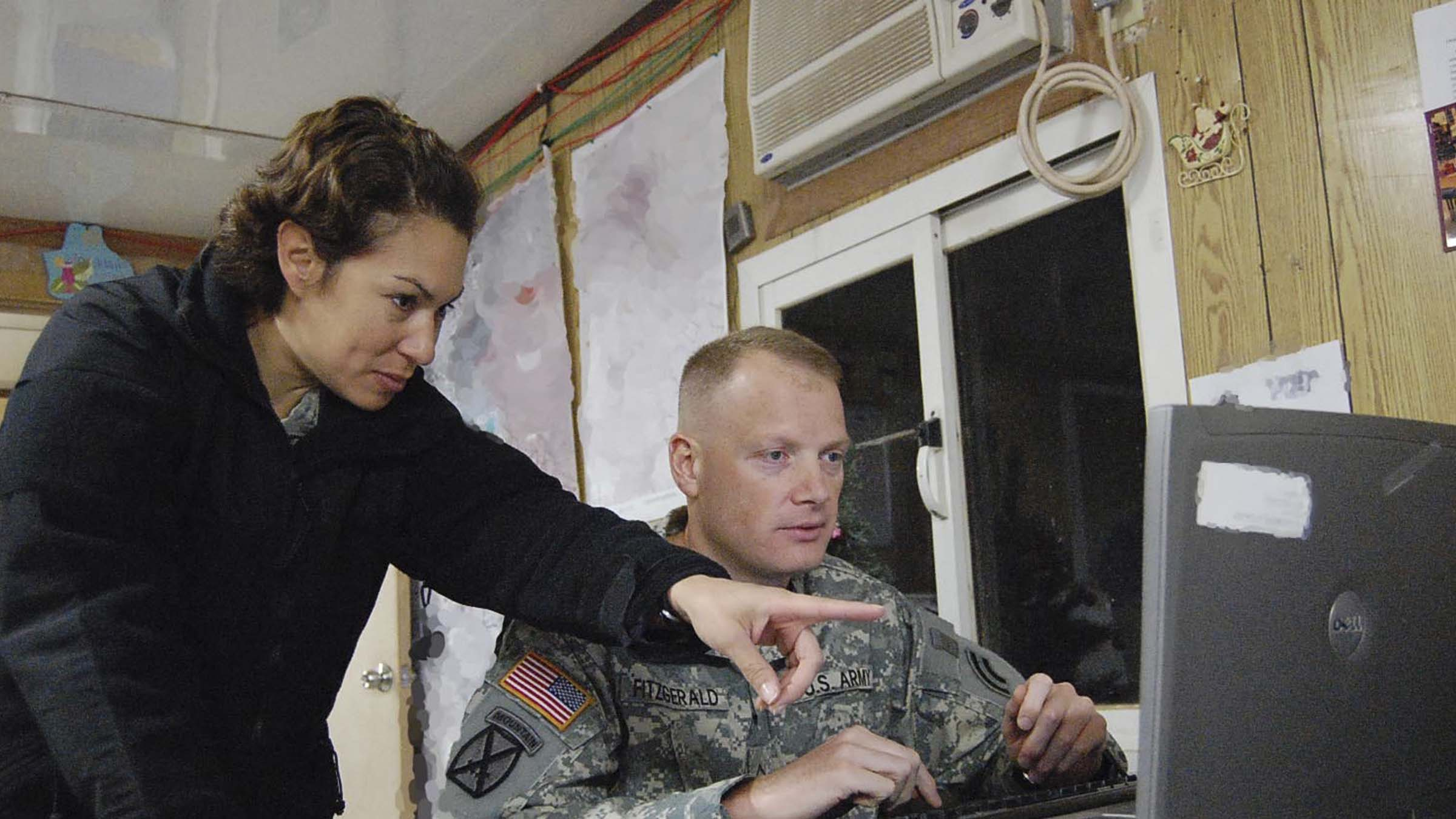 Woman and service member look at computer