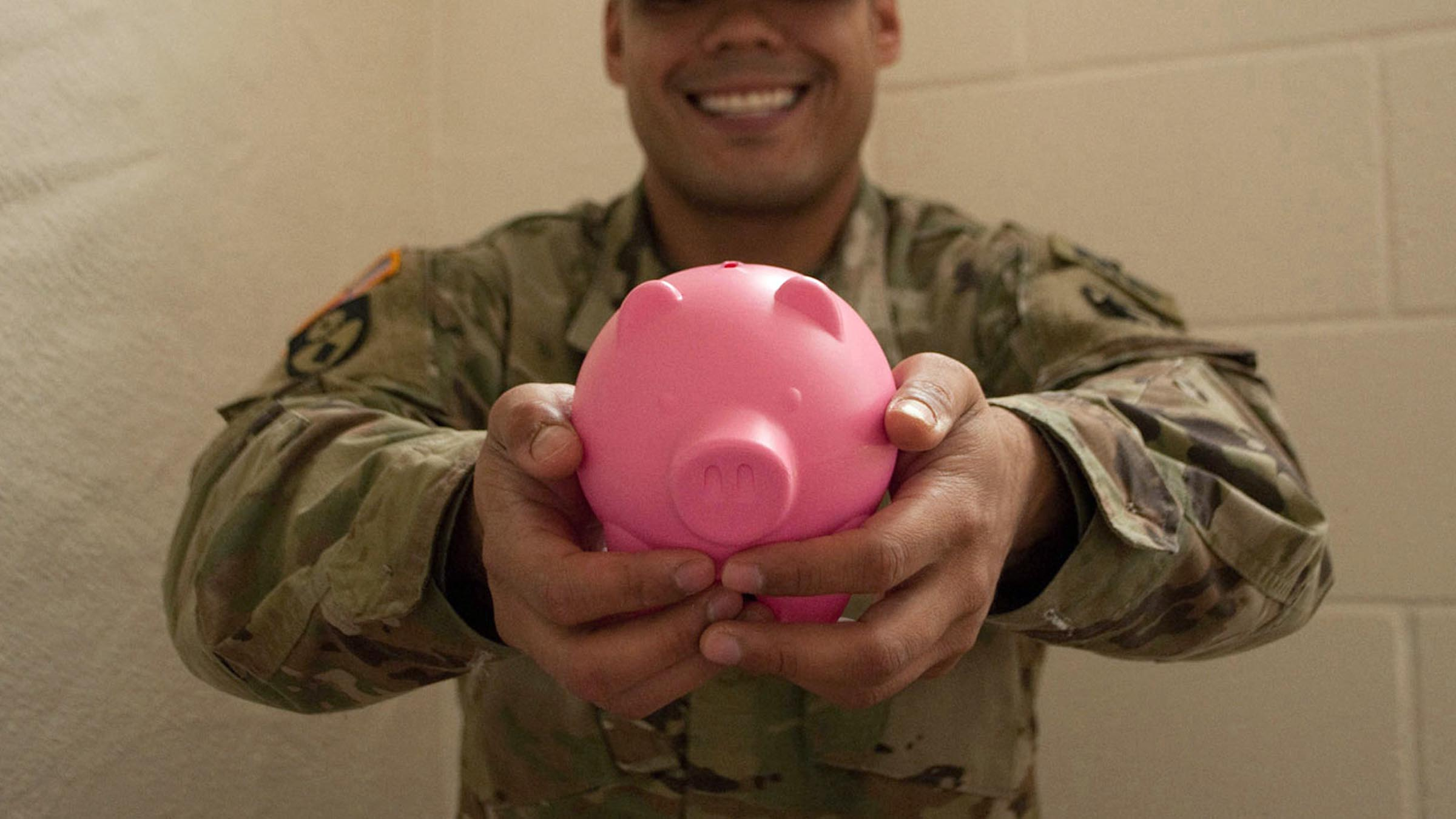 A service member smiles and holds up a pink piggy bank