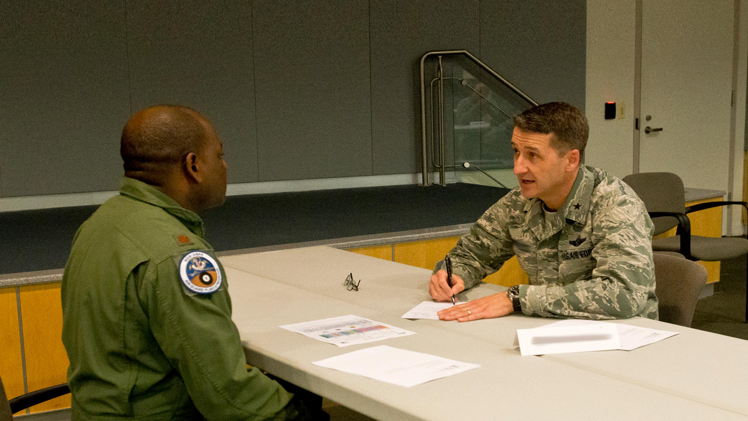 Two service members talking at table