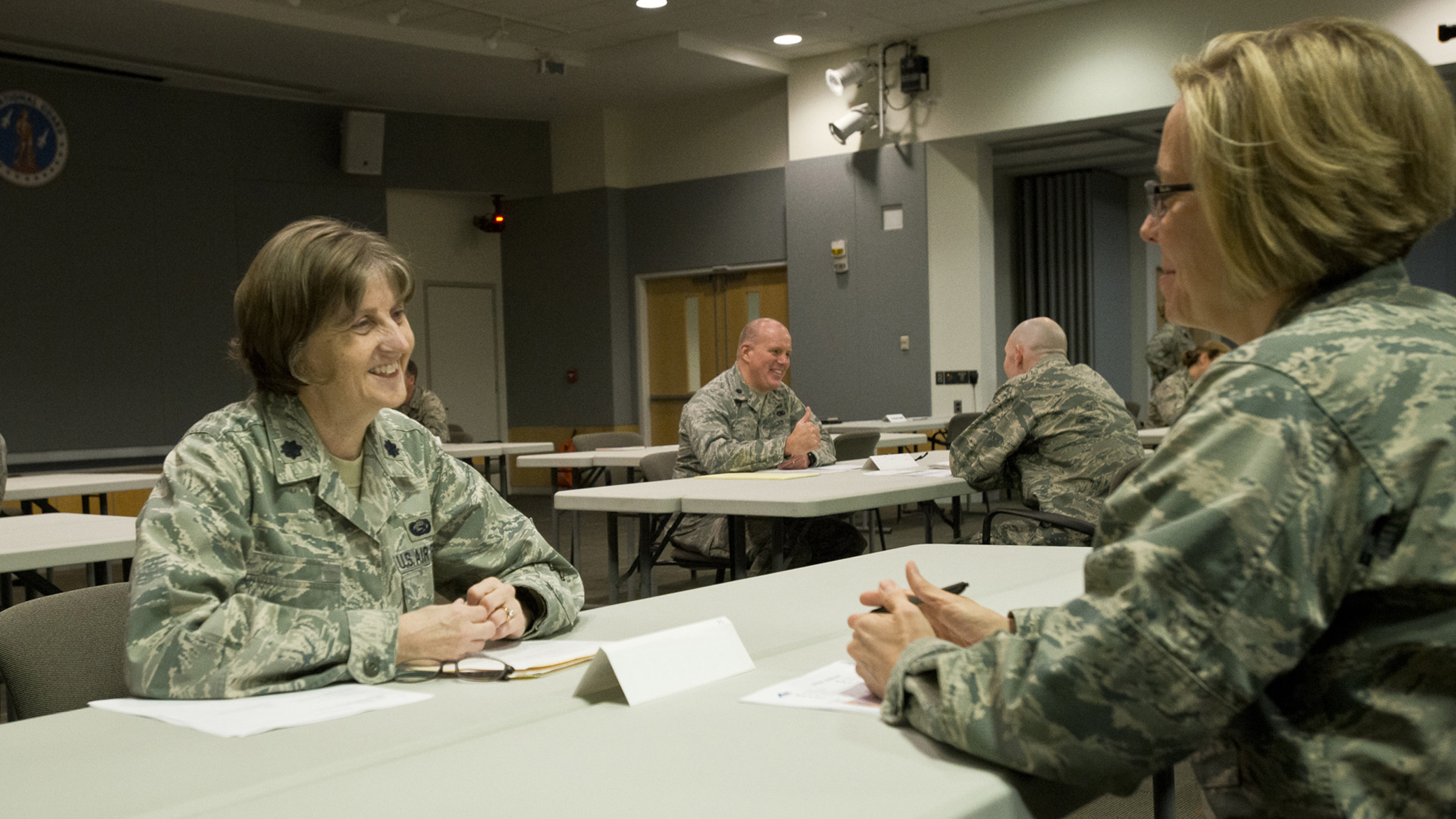 Two service members talking at a table