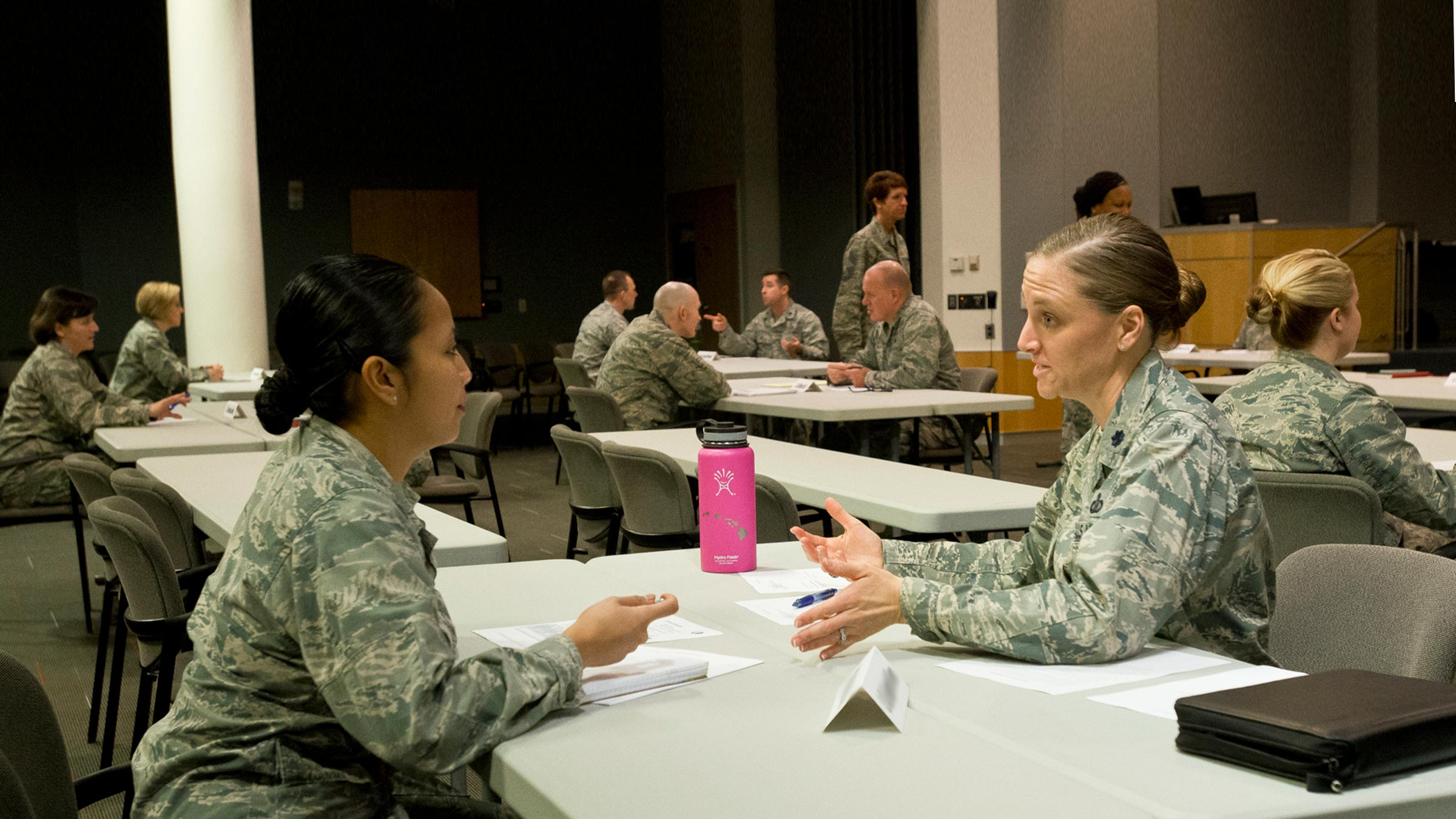 Two service members sitting at table talking