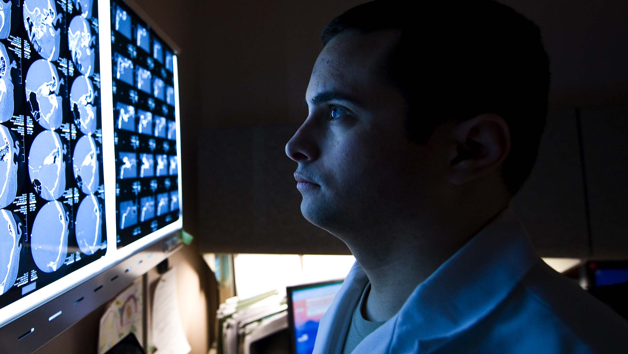 A military doctor studies a patient's computed tomography scan.