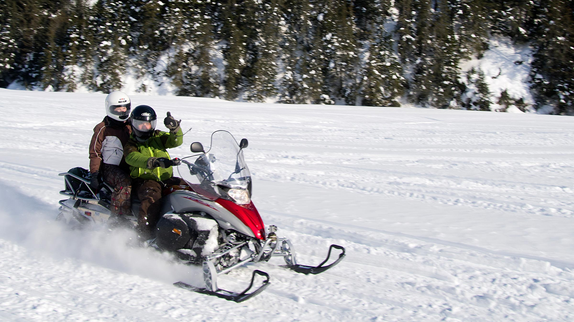 Two people ride on a snow mobile