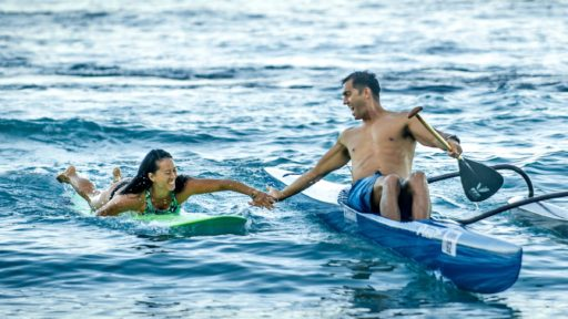 Man and wife enjoy surfing and paddle board