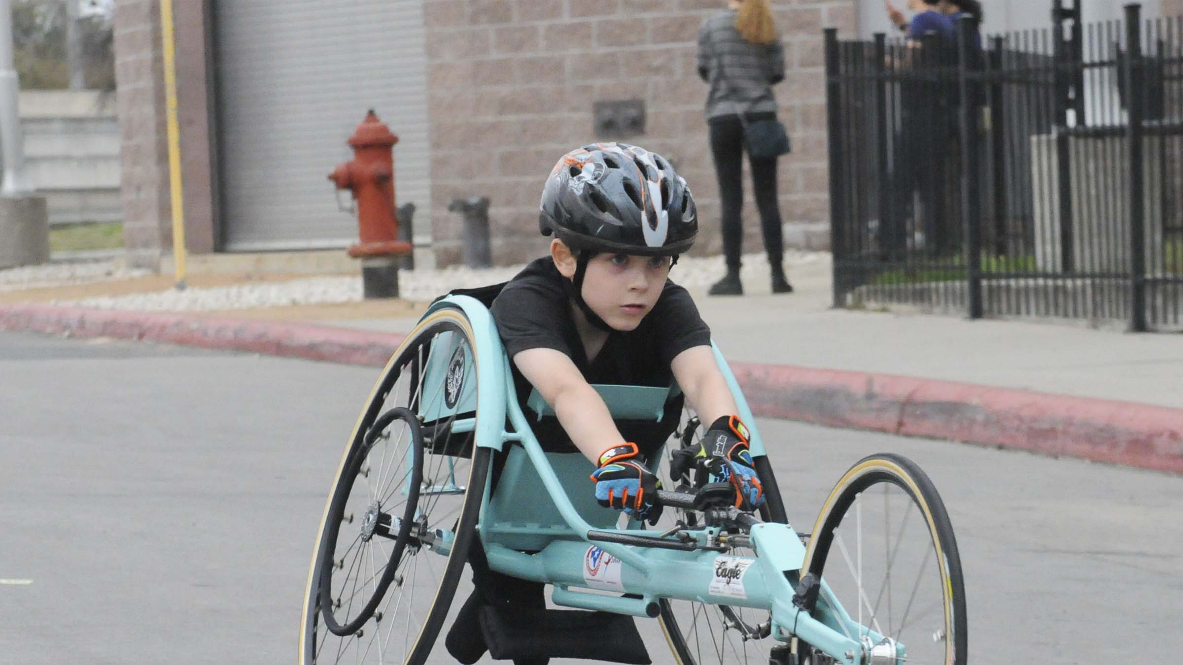 young athlete using a racing wheelchair
