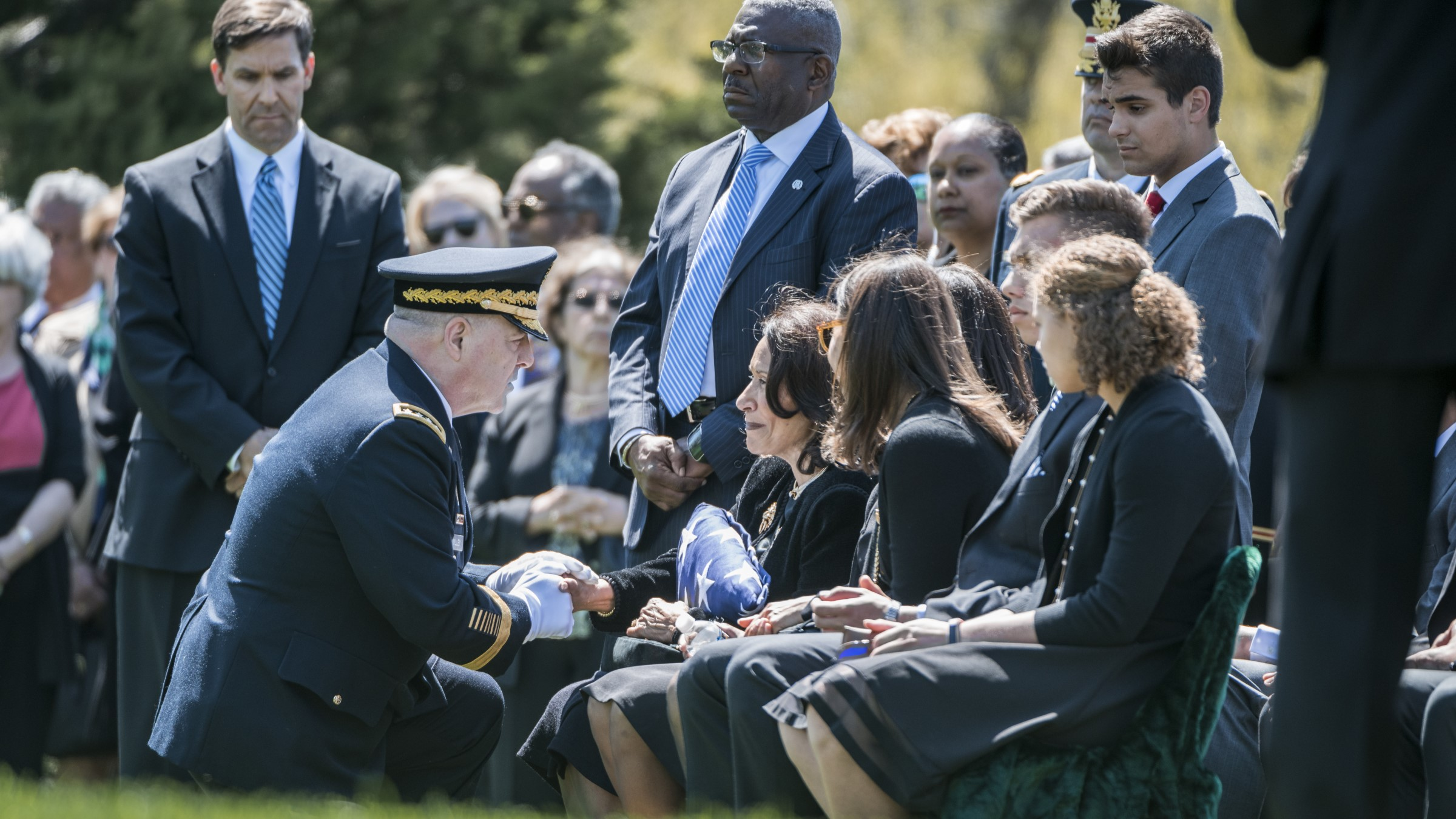 Army general gives burial flag to surviving spouse during her husband's funeral.