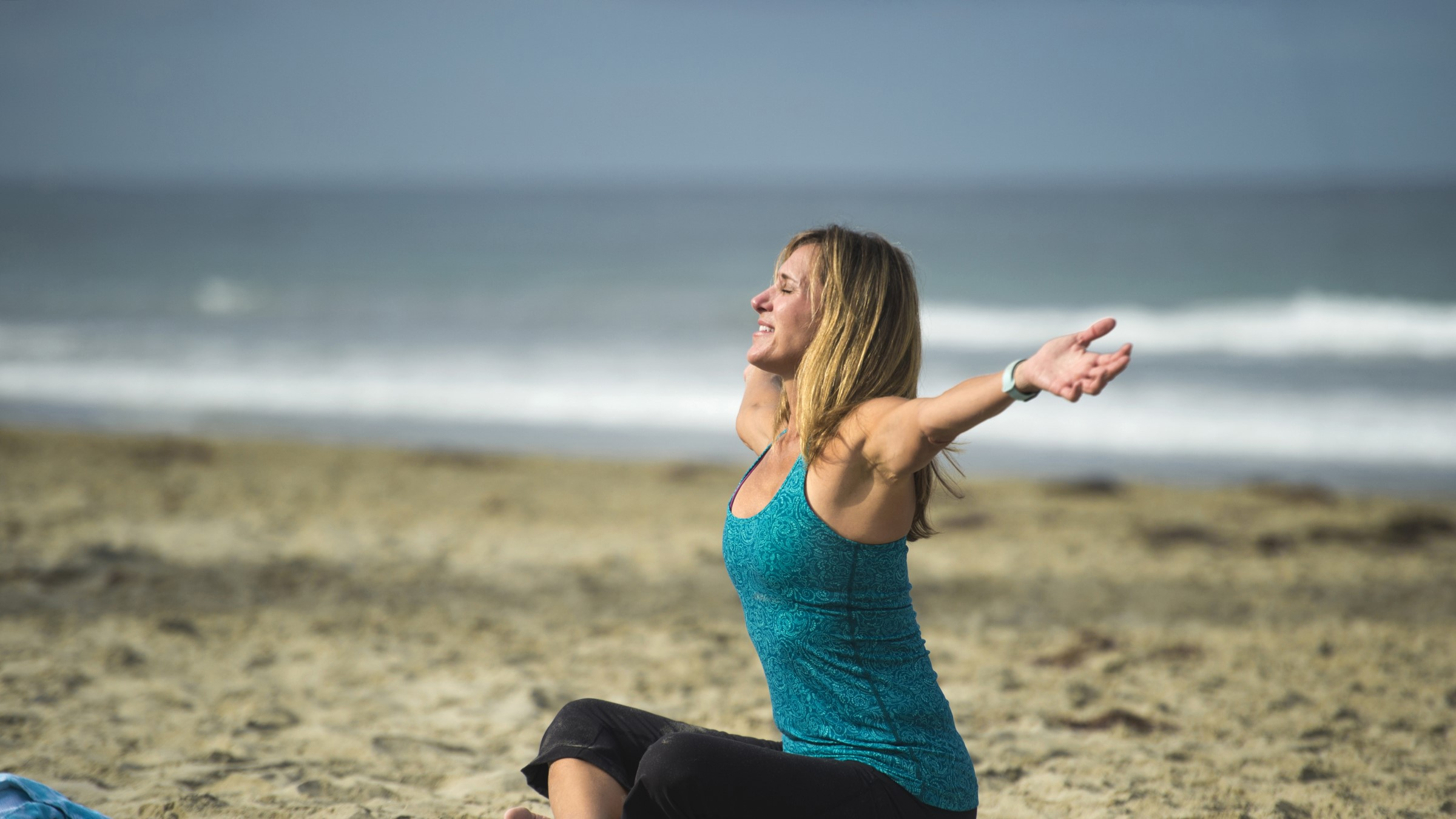 Woman participates in a yoga class on the beach.