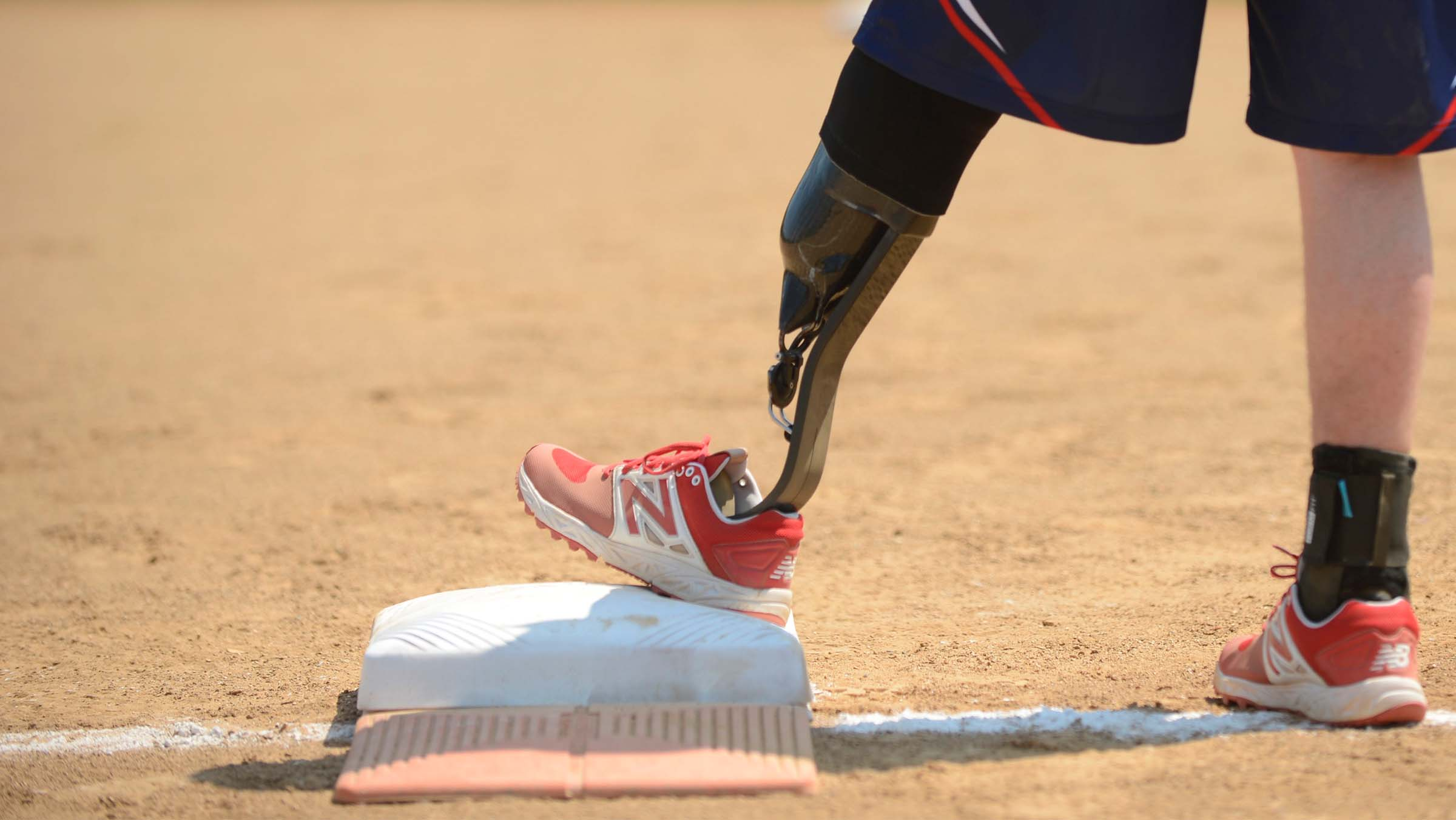 A Wounded Warrior Amputee Softball Team member stands on first base.