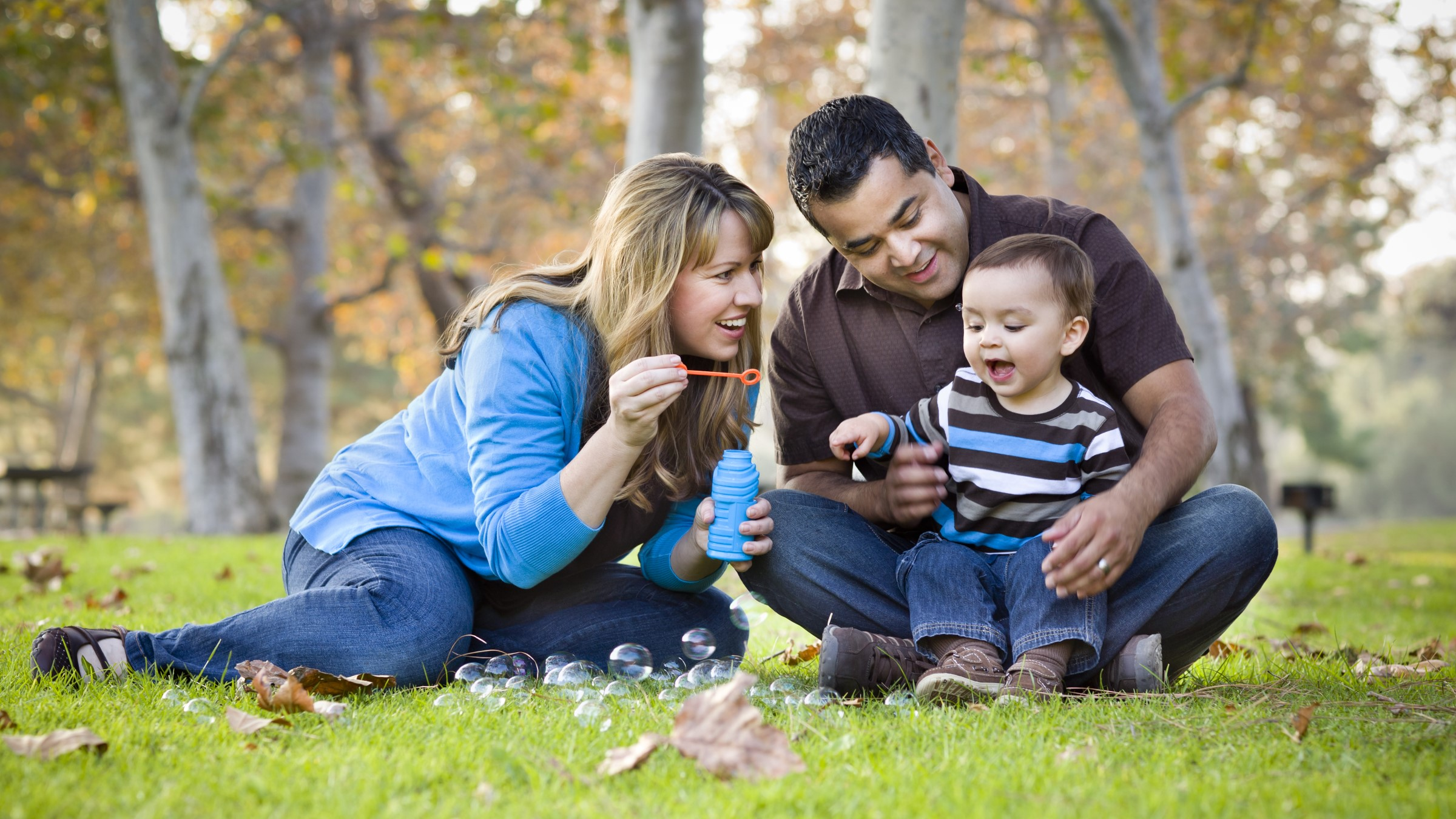 Young family blowing bubbles in the park