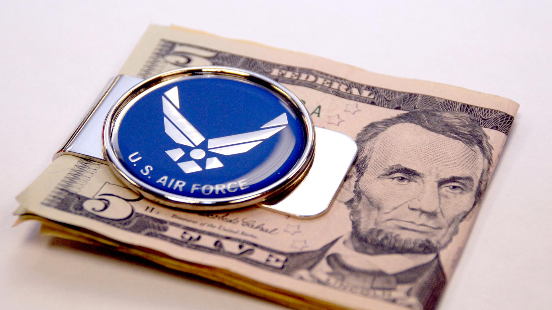 An Air Force money clip holds folded bills