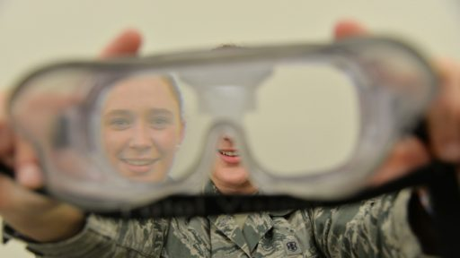 Airman holds out goggles to simulate drunken disorientation.