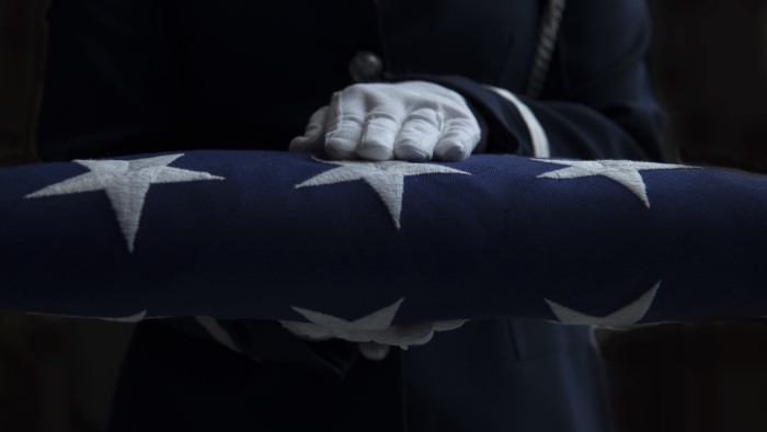 Hands holding a folded American flag
