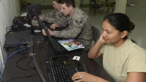 Service members working on laptops