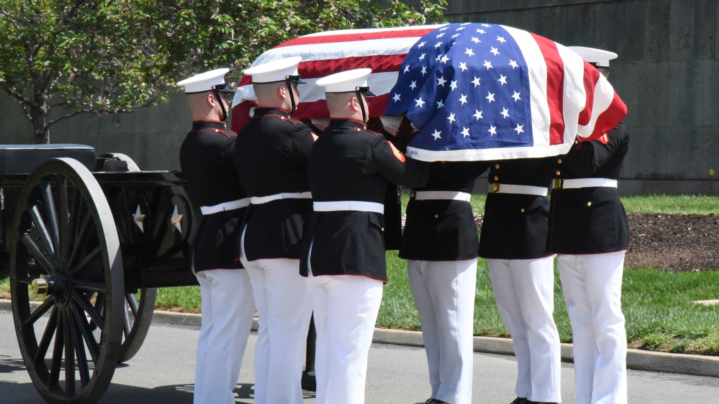 Marines carry flag-covered casket.