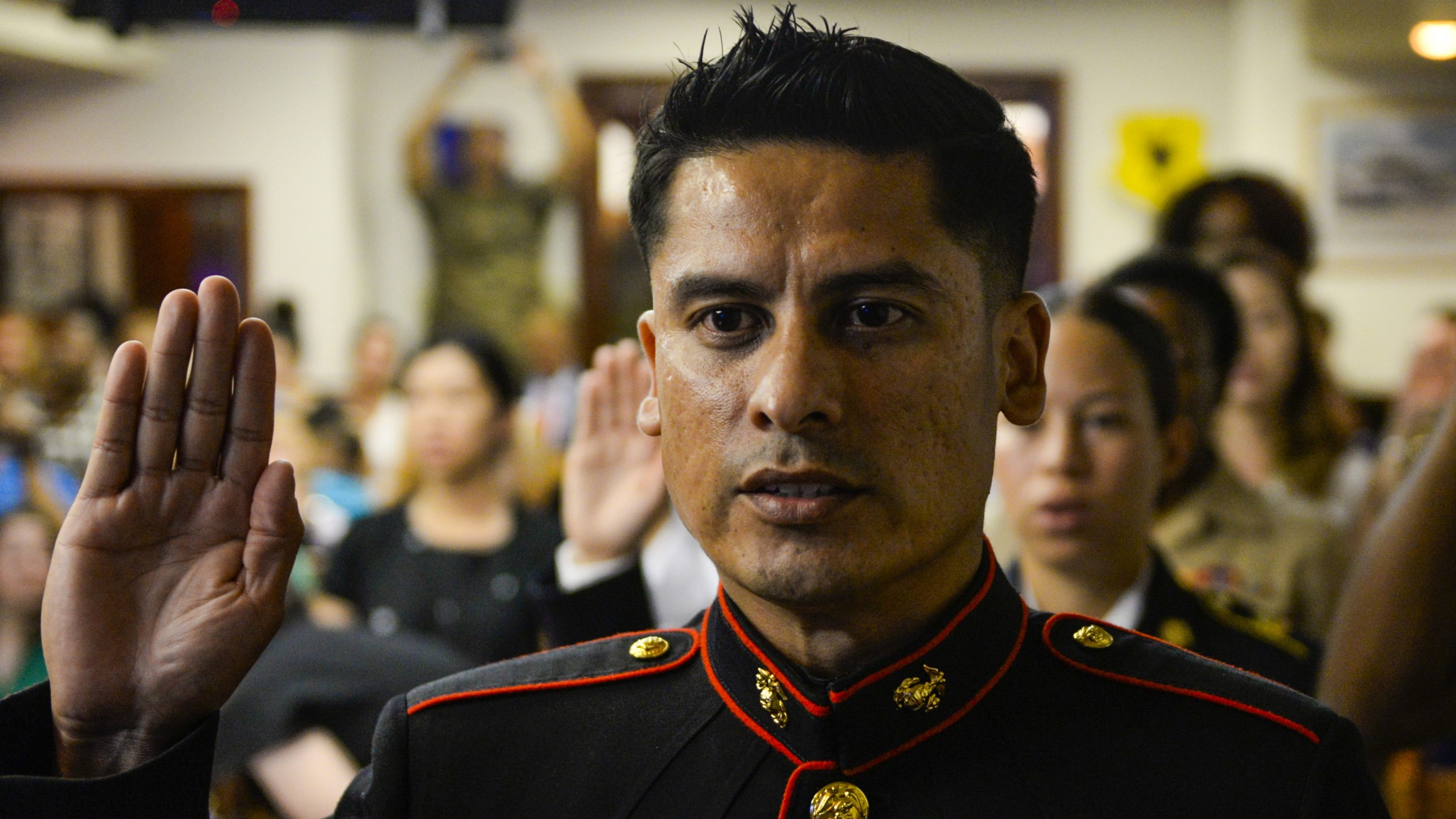 Marine Corps Staff Sgt. takes the oath of allegiance at a U.S. Naturalization ceremony at Kadena Air Base in Japan