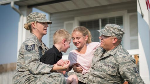 Military family of four playing in front of their house