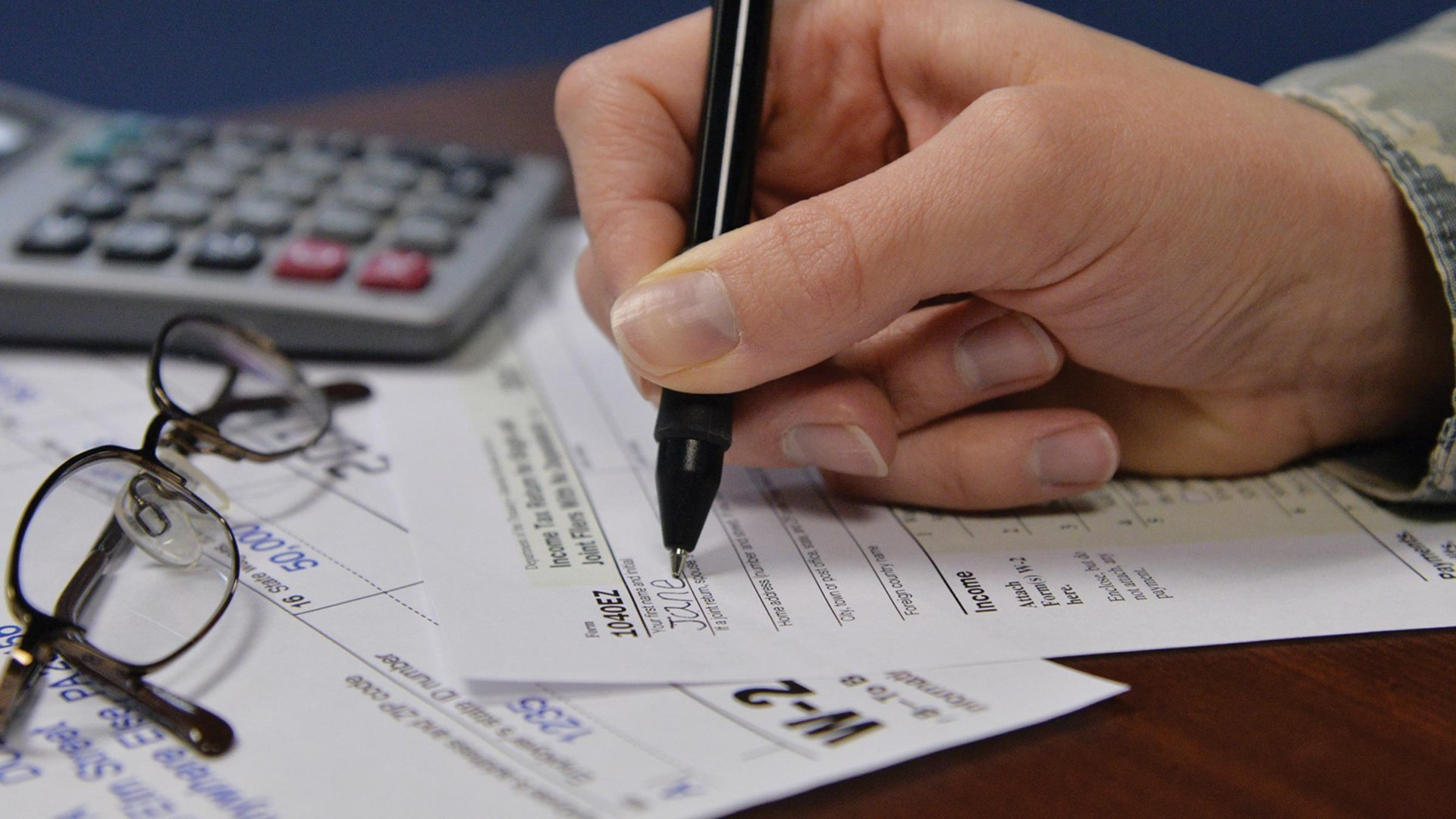 Military woman with calculator filling out tax paperwork