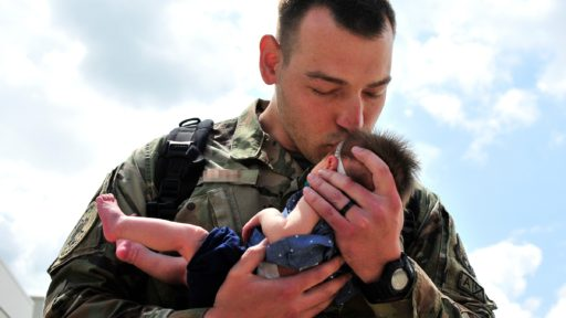 Service member embraces his newborn baby