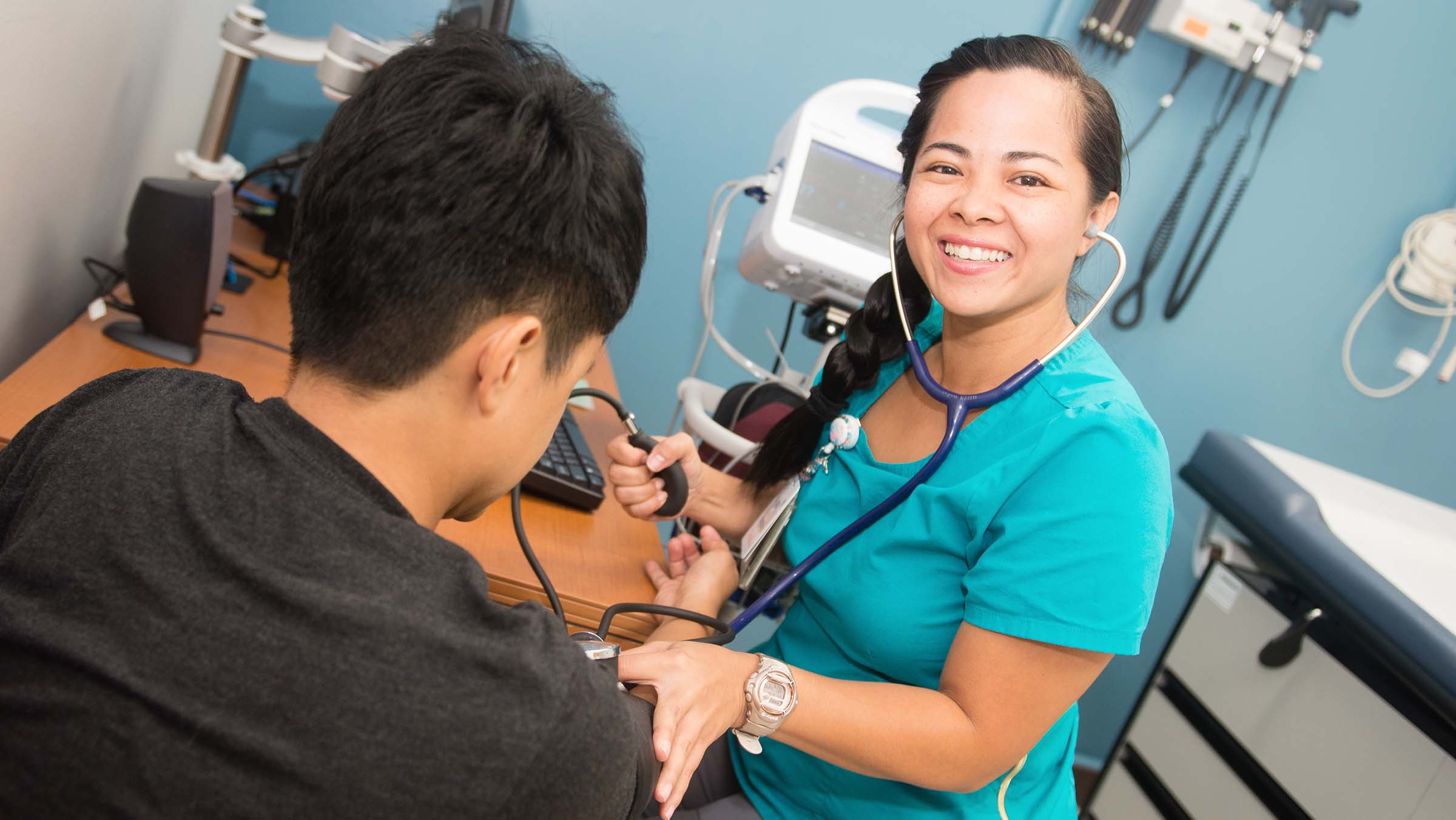 Nurse practitioner records a patient's vitals during a routine appointment