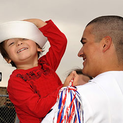 A service member with child wearing their hat