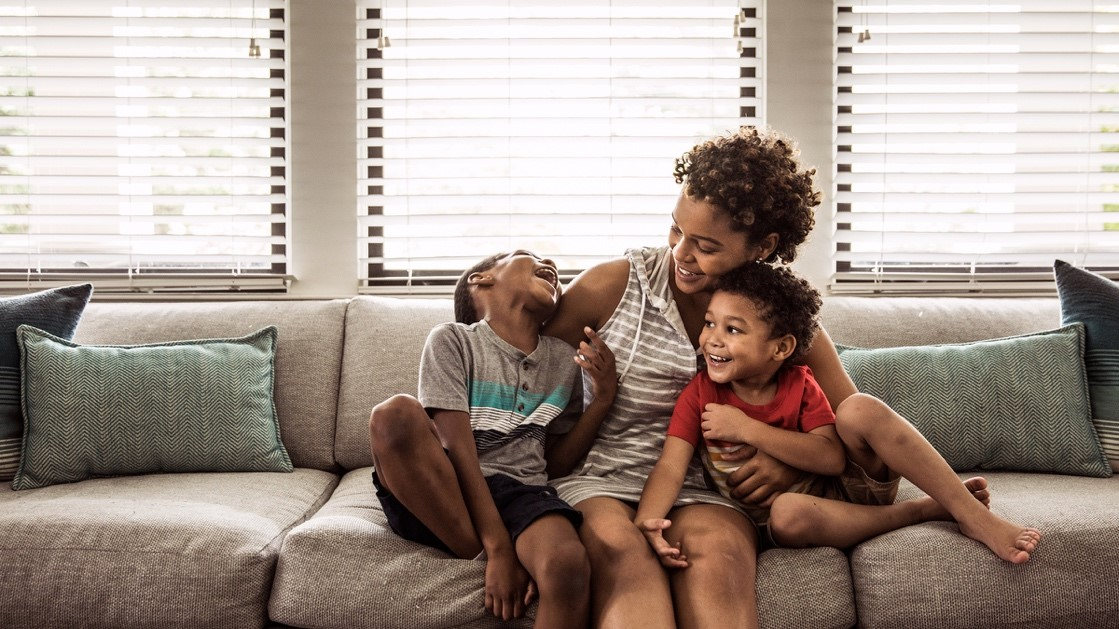 A woman sits with her children on a sofa.