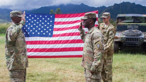 Service Member Reenlists in front of a Flag