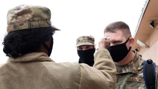 Service member taking deploying soldier's temperature