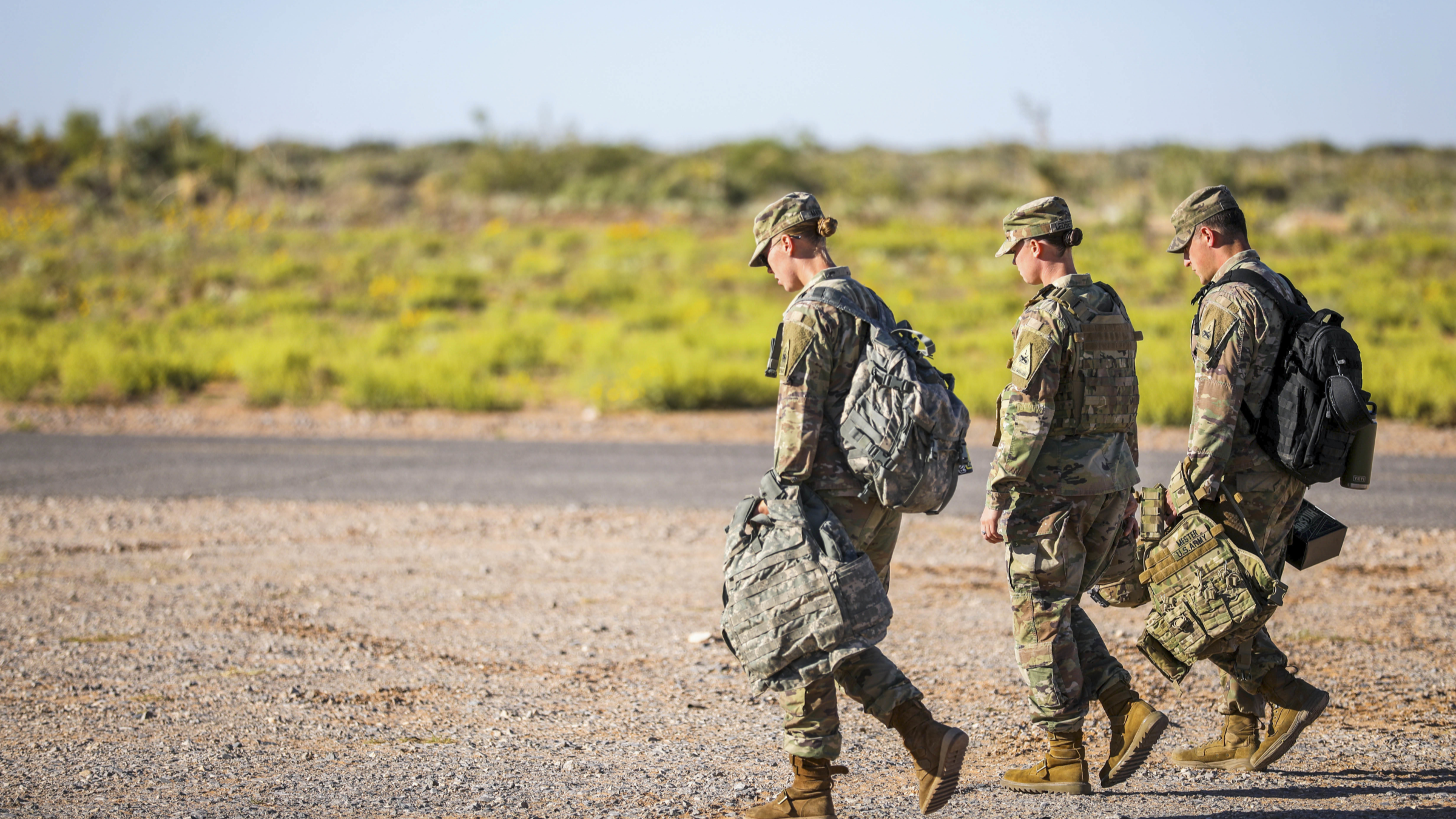 Service members walk with their equipment.
