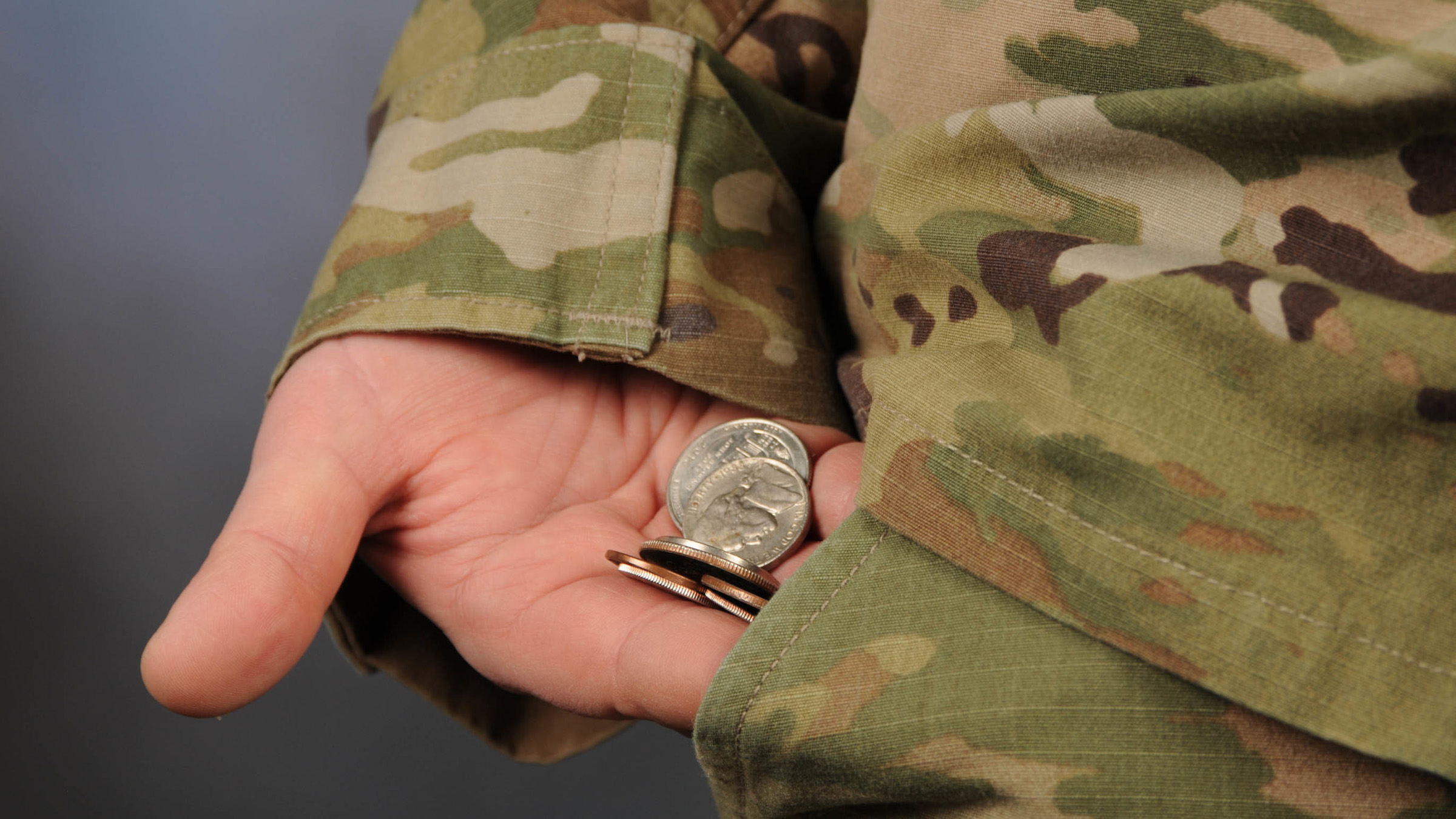 A servicemember counting out cash.