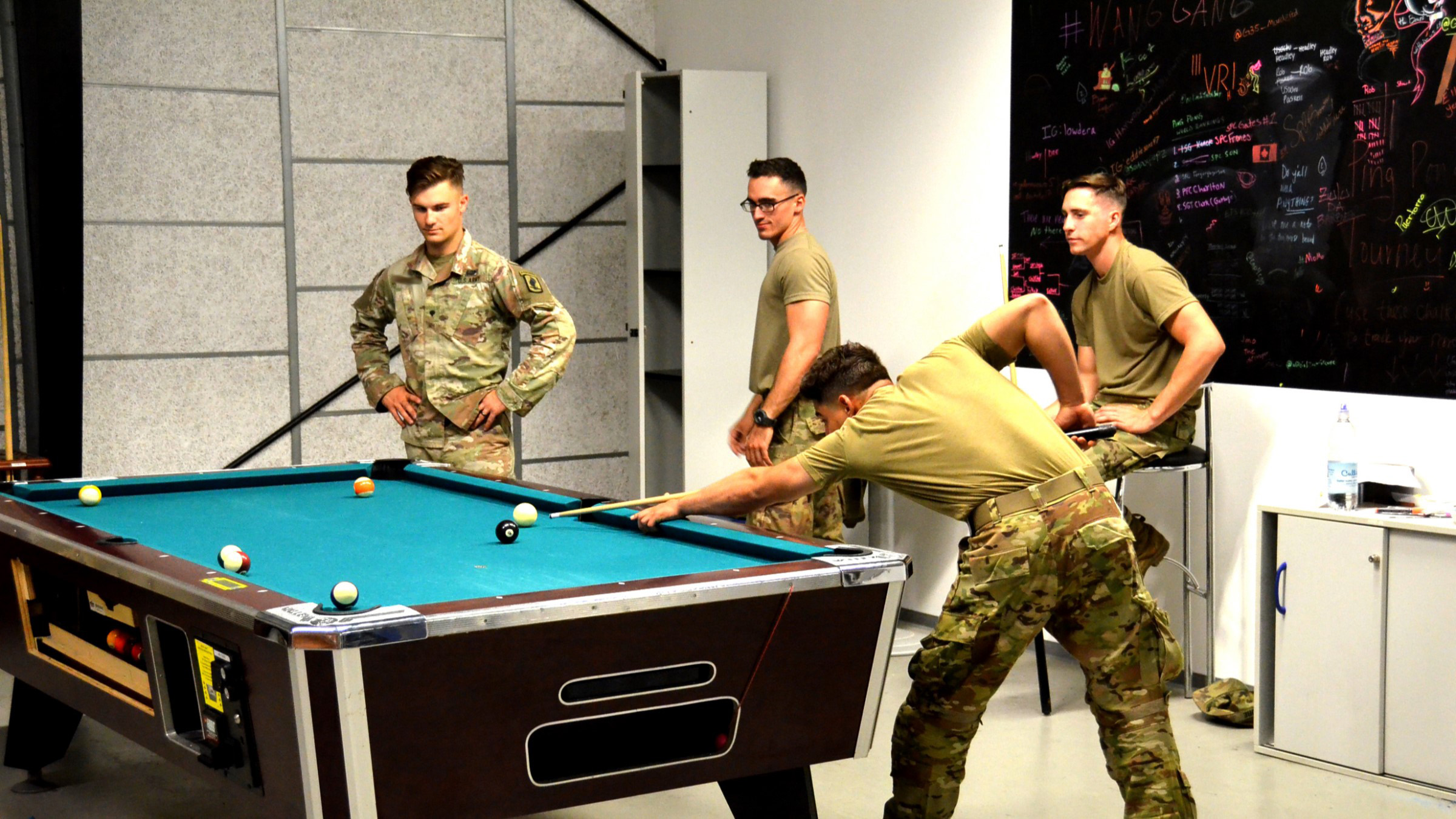 Service members playing a game of pool