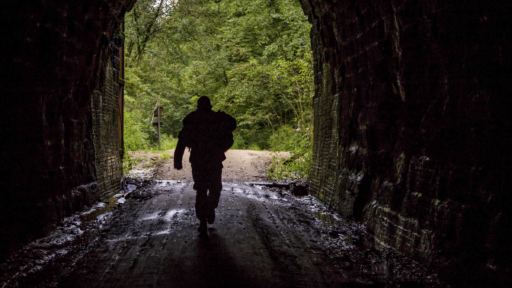 A soldier walks through a dark tunnel with a light and tree filled opening.