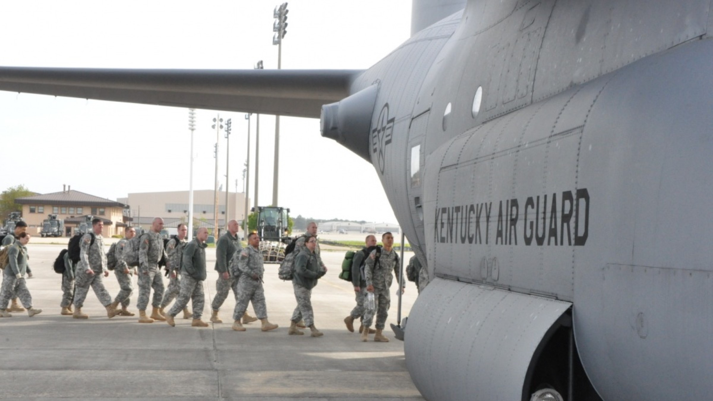 A group of National Guard soldiers board a military cargo plan after an exercise.