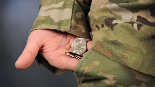Service member holding coins