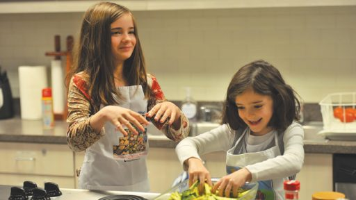 Two young girls cooking in a kitchen