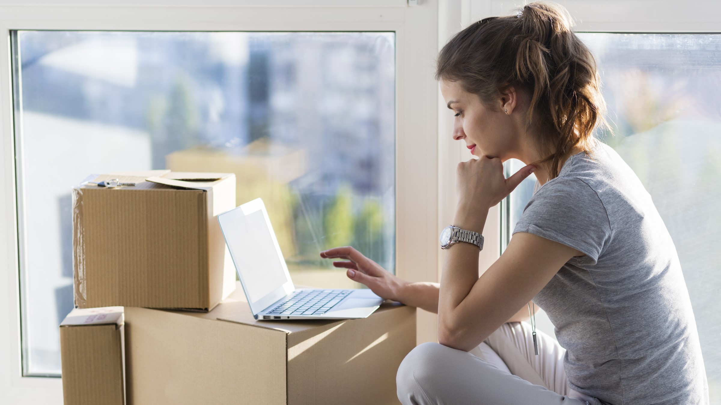 Woman works on computer at moving boxes